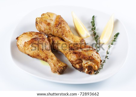 Roasted chicken legs with thyme and lemon on a plate