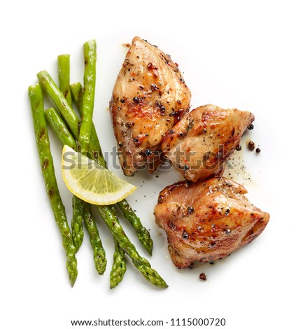 roasted chicken meat and grilled asparagus isolated on white background, top view