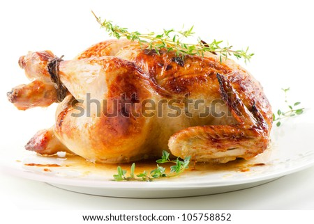 Roasted chicken on white plate with thyme