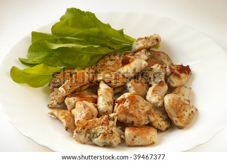 Roasted chicken seasoned slices over white parcel plate with rucola salad leafs