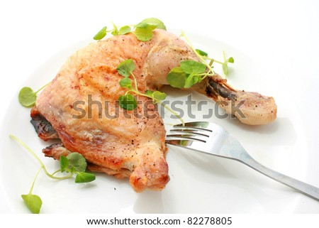 Roasted Chicken Thigh with fork isolated on white plate