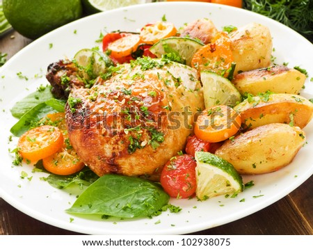Roasted chicken, vegetables, herbs and fruits. Viewed from above.