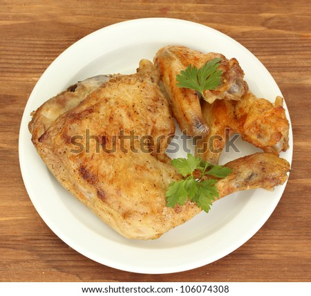 roasted chicken wings and leg with parsley in the plate on wooden background close-up
