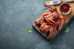 Roasted chicken wings in barbecue sauce with sesame seeds and parsley on a wooden board on a concrete table. Top view with copy space. Tasty snack for beer on a dark background. Flat lay