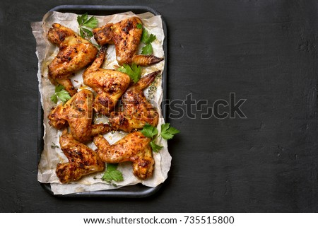 Roasted chicken wings on baking tray over dark background with copy space. Top view, flat lay
