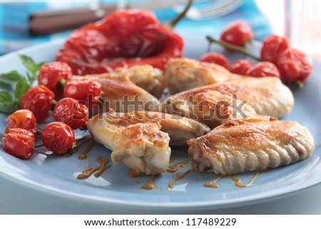 Roasted chicken wings with cherry tomatoes and baked pepper