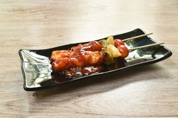 roasted chicken with pineapple chili and tomato dressing barbecue sauce stabbing wooden stick on plate
