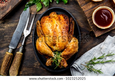 Roasted chicken with rosemary served on black plate with sauces on wooden table, top view