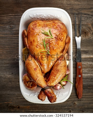 roasted chicken with vegetables on wooden table, top view