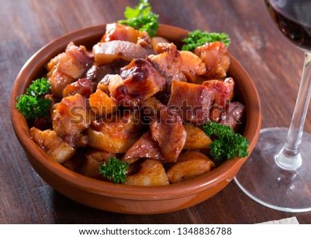 Roasted chopped pig snout served with leaves of parsley on clay bowl