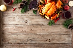 Roasted Christmas Chicken or Turkey for Christmas Dinner. Festive decorated wooden table for Christmas Dinner with baked chicken, top view, copy space.