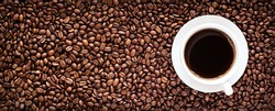 Roasted coffee bean background with a cup of hot espresso in the right side. Horizontal panorama banner with copy space