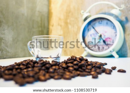 Roasted coffee beans and clock background.Cup of coffee with clock on its surface. Coffee time, coffee break concept #1108530719
