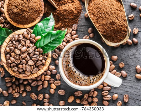 Roasted coffee beans, ground coffee and cup of coffee on wooden table. Top view. #764350033
