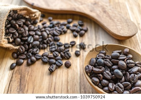 Roasted coffee beans in a sack are placed on a wooden floor. Some coffee beans are on the floor. Close up view of coffee beans. Photo taken with natural light