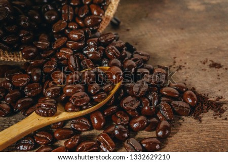 Roasted coffee beans in a sack bag and put in a spoon on an old wooden table. #1332629210