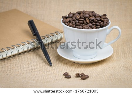 Photo of Roasted coffee beans In a white coffee cup and a pen with a brown notebook and the bottom surface is a brown fabric and a few coffee beans scattered on the floor and the image has some free space
