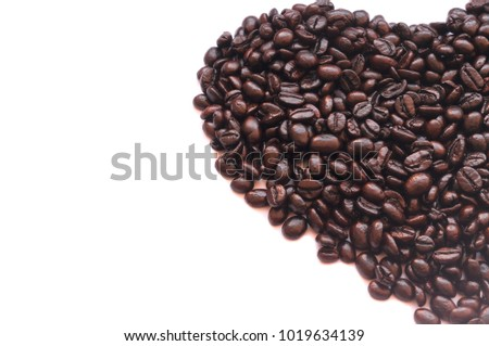 Roasted coffee beans in half heart shape on white background, isolated picture