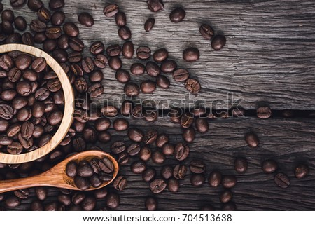 Roasted coffee beans in wooden cup and wooden spoon on wood background #704513638