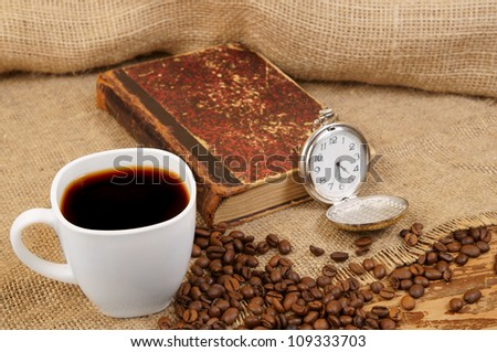 Roasted coffee beans, old book, watch and cup on jute background
