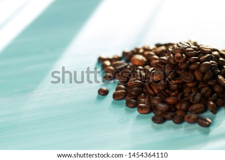 Roasted coffee beans on a blue background.