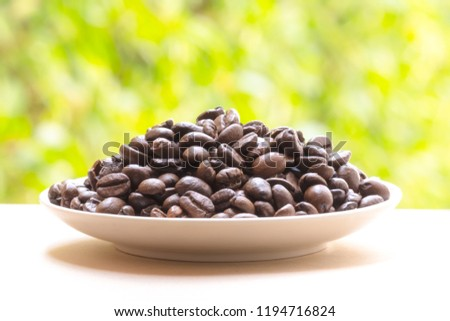 Roasted coffee beans on white plate of nature blur Background. #1194716824
