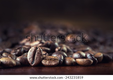 Roasted coffee beans spilled freely on a wooden table.Coffee time