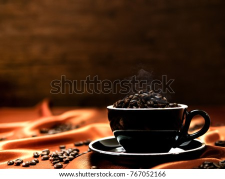 Roasted coffee beans with aroma smoke in a cup and some coffee beans scattered around on the brown fabrice texture with gradient blurred background #767052166