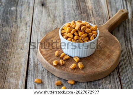 Roasted corn snack. Corn nuts with sauce on wood background. Bulk corn nut grains. Roasted corn nuts on a ceramic plate