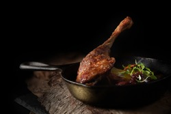Roasted duck leg in iron skillet with roasted potatoes and cherry plum sauce with a thyme garnish. Shot against a dark, rustic background with selective focus, generous accommodation for copy space.