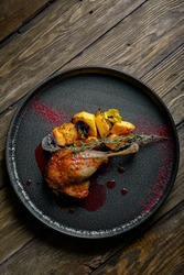 Roasted duck leg with confit pumpkin, closeup. Horizontal top view, top shot. Copy space, wooden background, low key