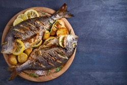 Roasted fish and potatoes, served on wooden tray. overhead, horizontal, copy space - image