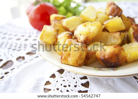 Roasted golden crispy potatoes on a ceramic dish
