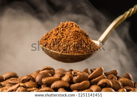 Roasted ground coffee into an old silver spoon and roasting coffee beans with smoke steam on dark background. Close-up photo. Vintage style effect picture, with copy space.