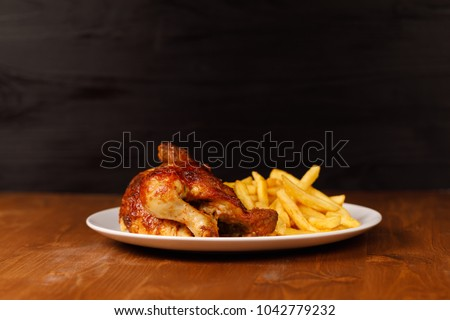 roasted half chicken, traditional bavarian dish with french fries on wooden table, and black copy space