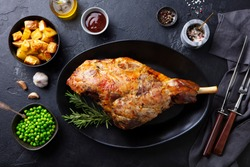 Roasted lamb leg with potato and green peas. Black background. Top view.