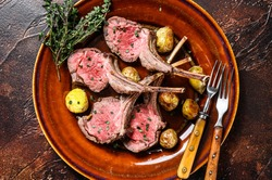 Roasted lamb meat rib chop steaks with potato. Dark background. Top view.