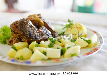 Roasted lamb plate with meat and baked potato salad