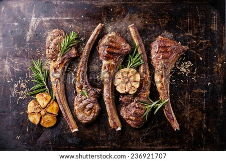 Roasted lamb ribs with spices and garlic on dark textural background - stock photo