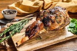 Roasted lamb, sheep leg on a cutting board with rosemary. wooden background. Top view