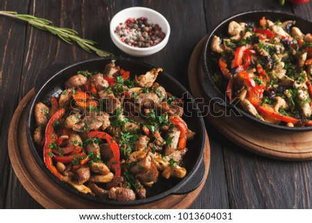 Roasted meat and vegetables on wooden table. Portion of stewed ragout with red sweet pepper and parsley, closeup