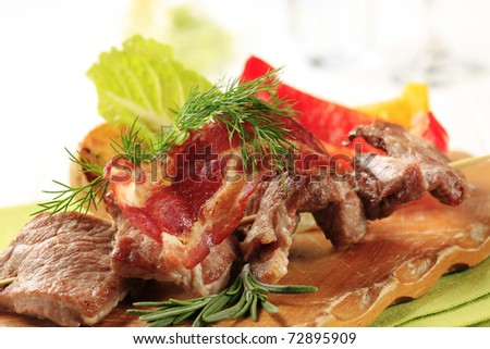 Roasted meat on wooden skewer and crispy bacon