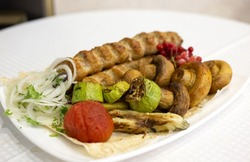 Roasted meat with grilled vegetables and mushrooms on white plate