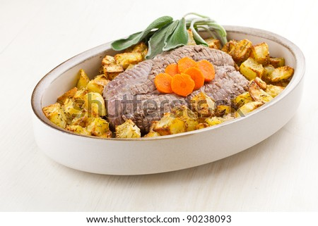 Roasted  meet and potatoes with sage and carrots garnish in dish over a white wood table