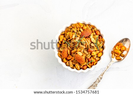 Roasted Mixed Nuts in a White Bowl Garnished with Fresh Rosemary on White Background Directly Above. Healthy Eating, Healthy Food Photography.