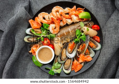 Roasted Mixed Seafood Contain Mussels, prawns, salmon, Calamari Squids and Grilled Barracuda Fish Garlic with Spicy Chili Sauce. Isolated on gray Background. Seafood and meat platter. Mediterranean