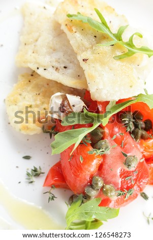 roasted peaces of fish with garnish on white background
