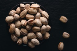 Roasted pistachios on the dark background. Dark food photography. Top view.