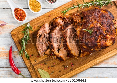 Roasted Pork shoulder cut on slices on chopping board on white peeling paint boards with garlic, chili and spices,view from above #520108441