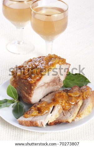 Roasted pork with apricot sauce on a plate and two glasses of wine - stock photo